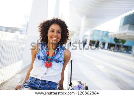 Portrait of a young black woman, fashion model wearing short jeans with afro hairstyle in train station - stock photo
