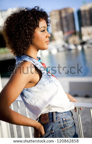 Portrait of a young black woman, fashion model wearing short jeans with afro hairstyle in urban background - stock photo