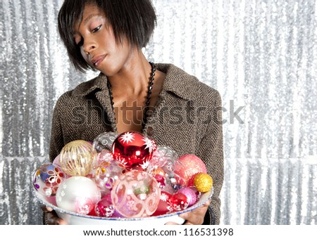 Portrait of a young black woman holding a dish full of christmas bar balls against a silver sequins background. - stock photo