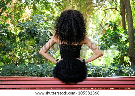 Portrait of a young black woman, model of fashion in a garden - stock photo