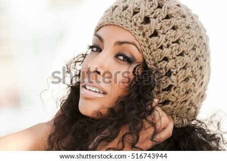 Portrait of a young black woman smiling with braces . Girl wearing wool cap.