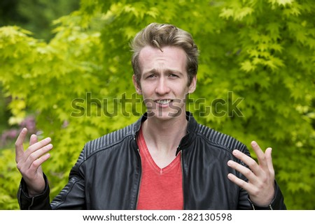 portrait of a young blond man in a black leather jacket looking angry - stock photo