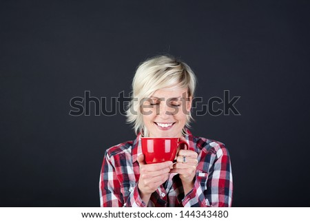 Portrait of a young blond woman enjoying coffee against black background - stock photo