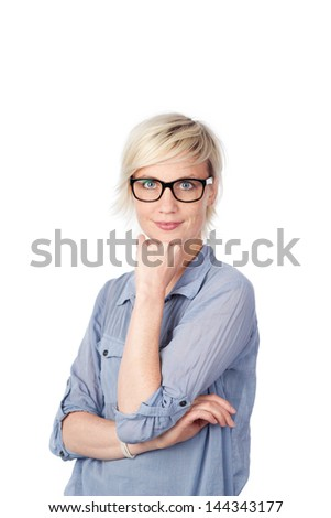 Portrait of a young blond woman in blue shirt standing with hand on chin against white background