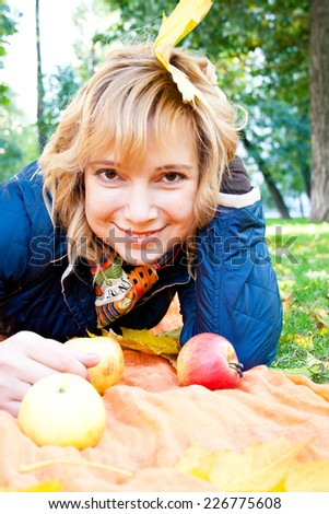 Portrait of a young blond woman lying on the grass with apples and autumn leaves