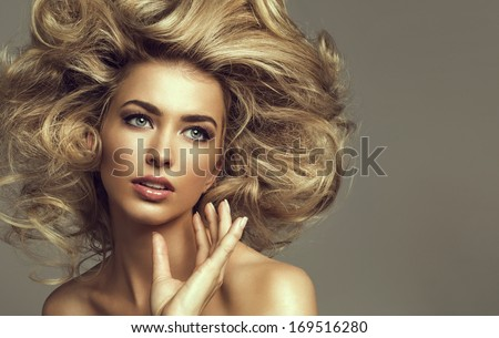 Portrait of a young blond woman with beautiful hair and green eyes - stock photo