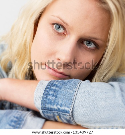 Portrait of a young blond woman with jeans jacket looking with a soft smile and lying on her arms, studio fashion shot with a selective focus at the eyes