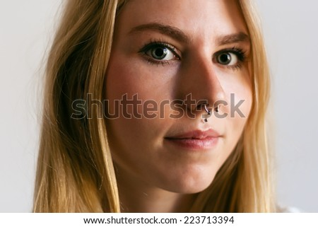 Portrait of a young blonde girl with nose piercing