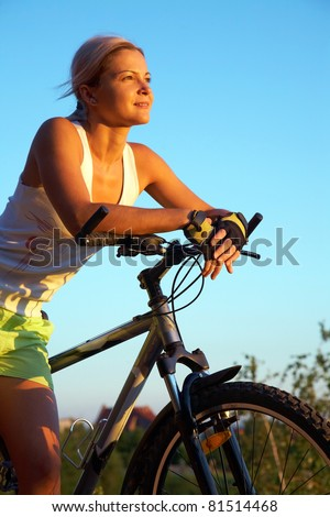 Portrait of a young blonde girl with sporty mountain bike - stock photo