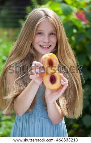 Portrait of a young blonde little girl with peach, summer outdoor