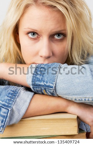 Portrait of a young blonde woman, as female student looking frustrated and leaning on her books, studio shot against a white background - stock photo