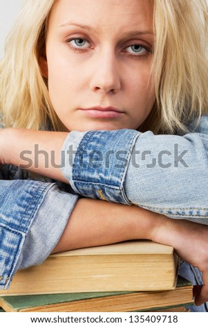 Portrait of a young blonde woman, as female student looking tired and leaning on her books, studio shot against a white background - stock photo