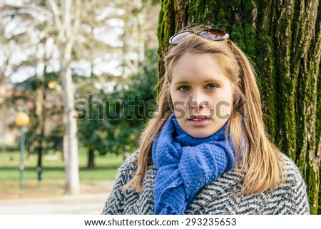 Portrait of a young blonde woman in a park during winter time