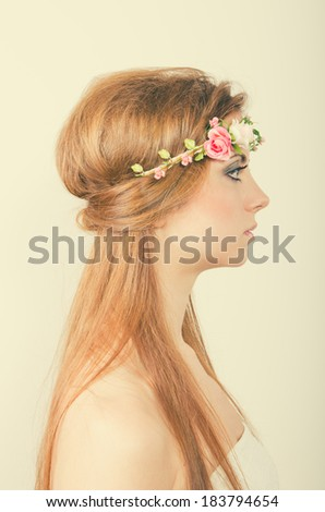 Portrait of a young blonde woman with long hair with a tiara of artificial roses. Side face. - stock photo