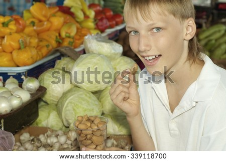 Portrait of a young boy choosing groceries  on market - stock photo