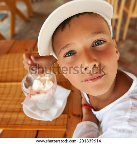 Portrait of a young boy eating a tasty ice cream outdoor. - stock photo
