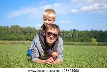 portrait of a young boy hugging his father in a meadow - stock photo