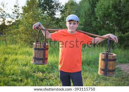 Portrait of a young boy in a cap with a yoke and wooden pails - stock photo