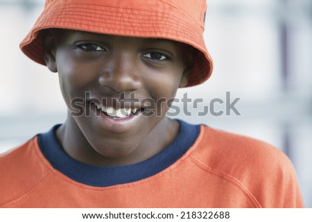 Portrait of a young boy in orange hat looking at camera - stock photo