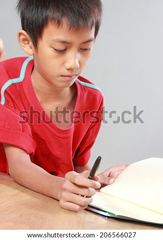 Portrait of a young boy lay down writing something on the book