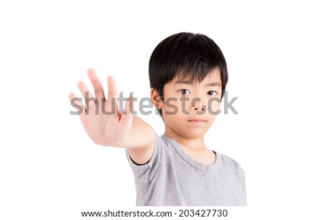 Portrait of a young boy making stop gesture on white background - stock photo