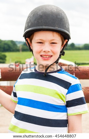 Portrait of a young boy wearing a horse riding hat