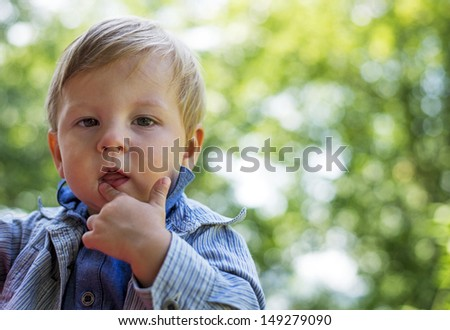portrait of a young boy with an interesting face outdoors