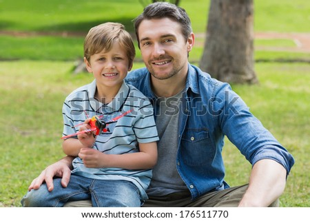 Portrait of a young boy with toy aeroplane sitting on father's lap at the park