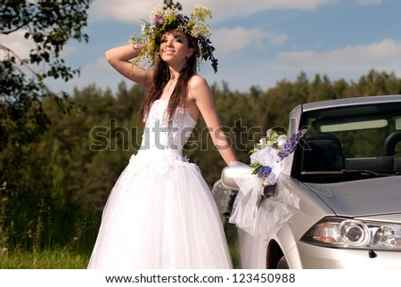 Portrait of a young bride near the cabriolet on the background of nature - stock photo