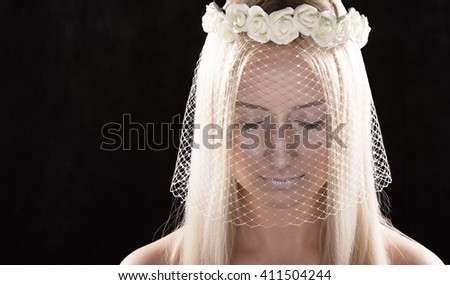 Portrait of a young bride with her eyes closed. Bright long hair. The veil and wreath of roses in her hair. The dark background - stock photo