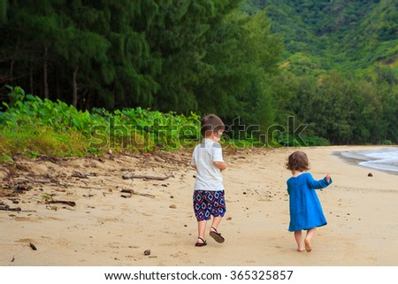 Portrait of a young brother and sister on the beach in Oahu Hawaii at Kahana Bay.