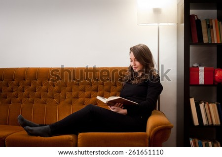 Portrait of a young brunette beauty immersed in reading a book. - stock photo
