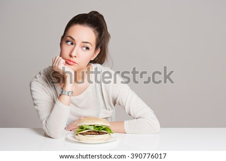 Portrait of a young brunette beauty offering nutrition choices.