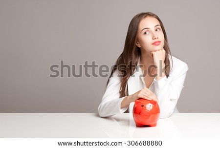 Portrait of a young brunette beauty with orange piggy bank. - stock photo