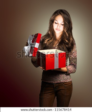 Portrait of a young brunette beauty with red gift box in creative lighting. - stock photo