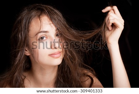Portrait of a young brunette beauty with shiny wet hair.