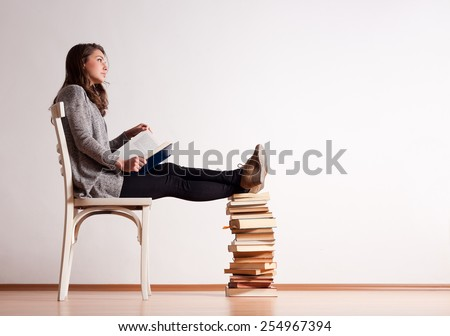 Portrait of a young brunette student with a large pile of books. - stock photo