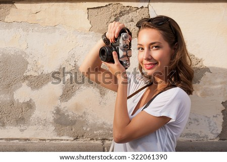 Portrait of a young brunette tourist woman taking photo. - stock photo