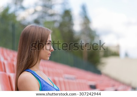 Portrait of a young brunette woman in profile at the stadium. - stock photo