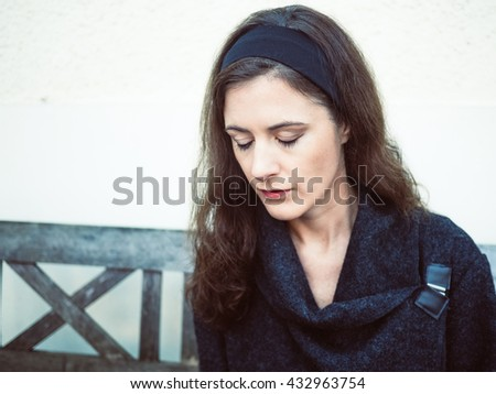 Portrait of a young brunette woman looking down and sitting on a bench outside - stock photo