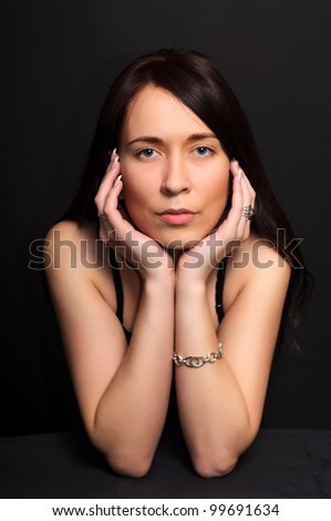 portrait of a young brunette  woman with arms crossed under her chin on dark black background - stock photo