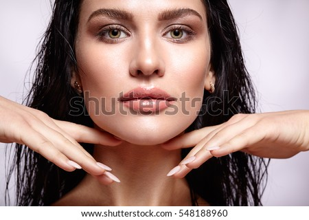 Portrait of a young brunette woman with shining wet make-up and shiny moist long hair hairdo