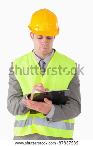 Portrait of a young builder taking notes against a white background - stock photo