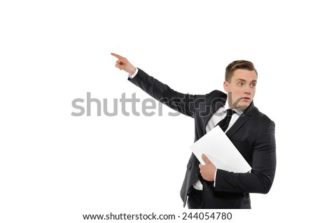 Portrait of a young business man holding magazine and pointing to the left. Concept of showing the right direction in business. Isolated on white background.