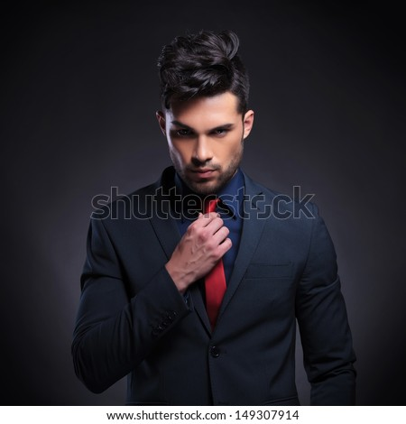 portrait of a young business man looking at the camera while fixing his tie. on a black background - stock photo