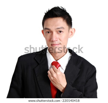 portrait of a young business man looking at the camera while fixing his tie. on a white background.