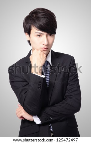 Portrait of a young business man looking depressed from work isolated over gray background, asian model
