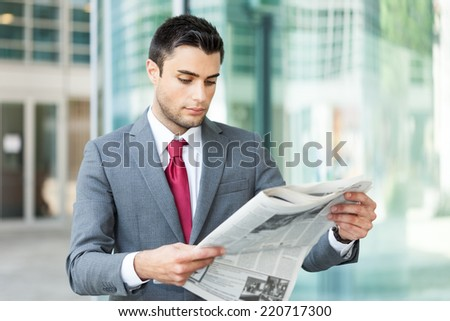 Portrait of a young business man reading a newspaper - stock photo
