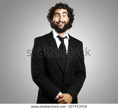 portrait of a young business man showing his tongue over a grey background