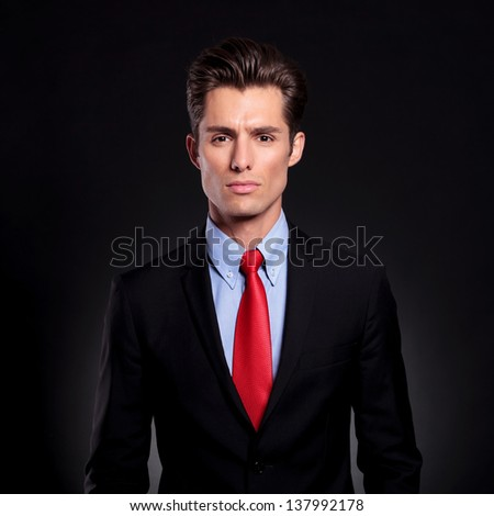 portrait of a young business man standing against a black background and looking at the camera with a straight face - stock photo
